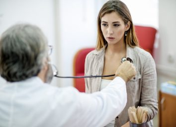 Young woman getting her chest examined by a doctor.