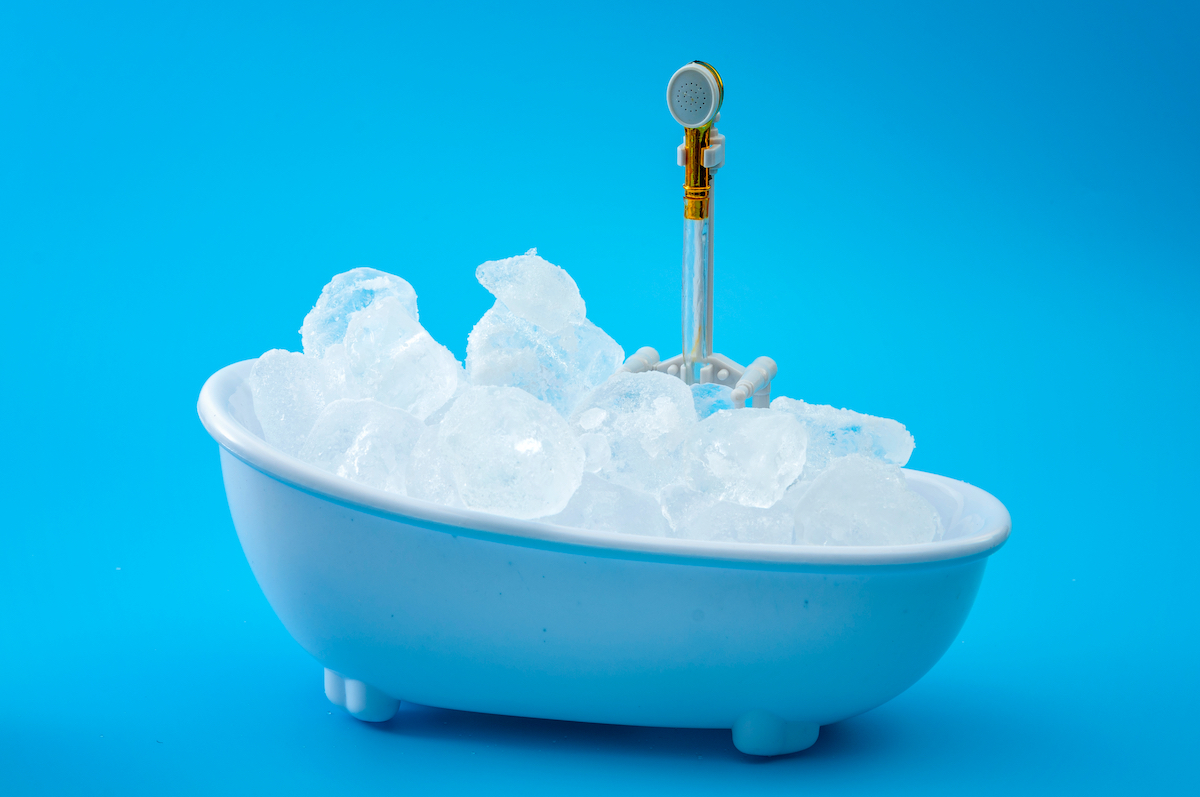 Muscle recovery and healing therapy, performance improvement treatment and extreme cold cryotherapy concept with minimalist bathtub filled with ice isolated on blue background