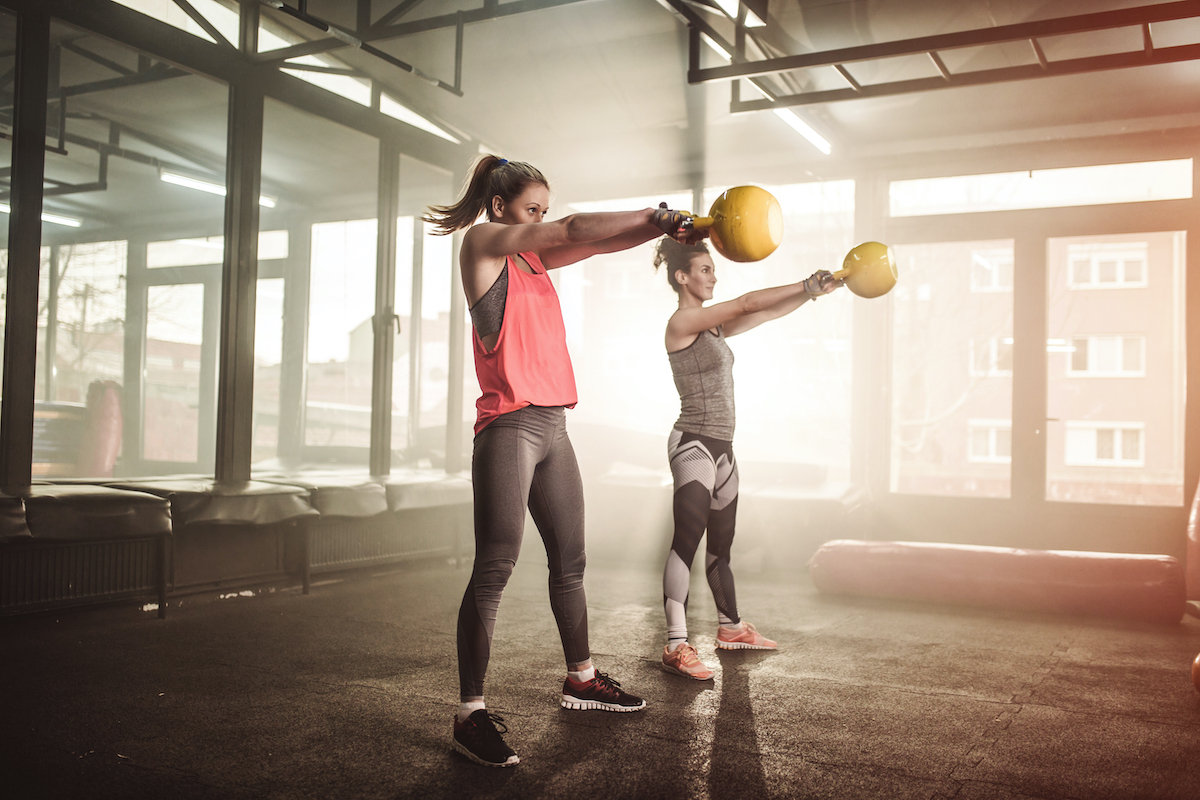 Two woman lifting kettle bell in cross fit gym