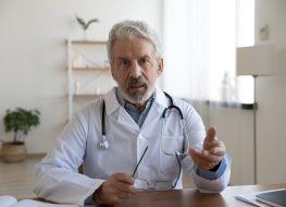 Mature doctor wearing uniform speaking at camera