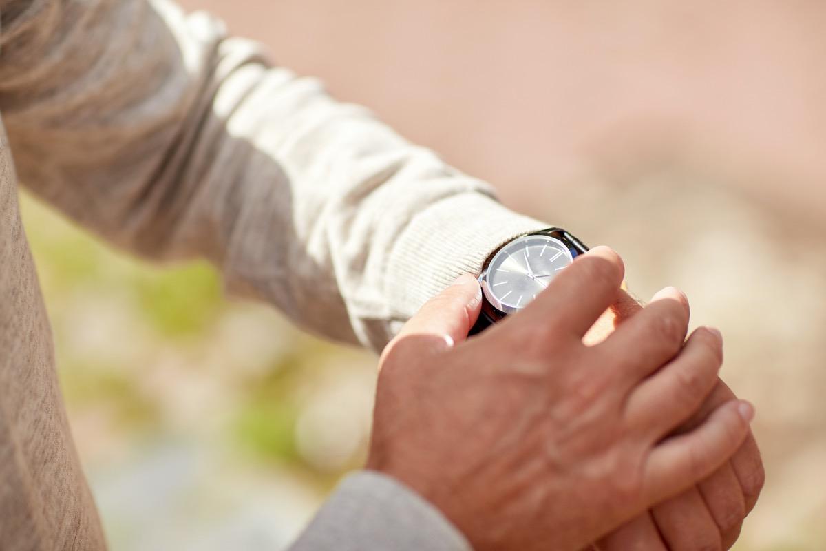 A senior man checking time on wristwatch outdoors.