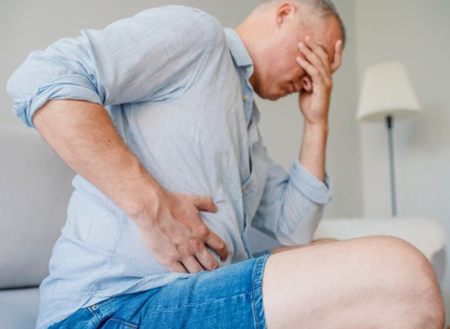 middle-aged man doubled over in liver pain