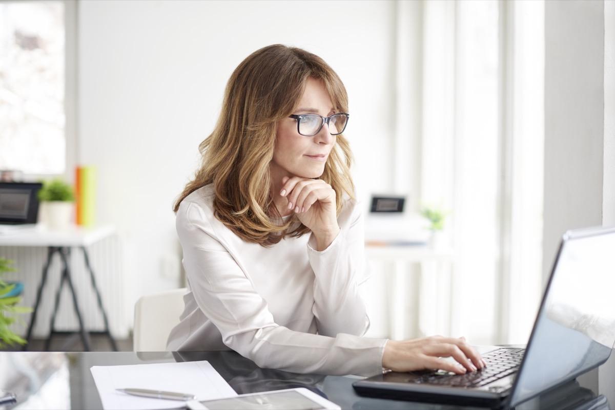 Mature businesswoman working on laptop in her workstation.