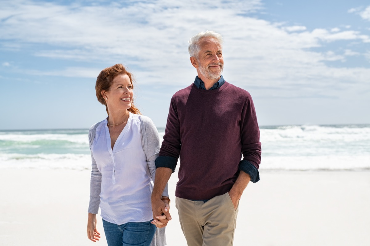 Senior couple walking on beach.