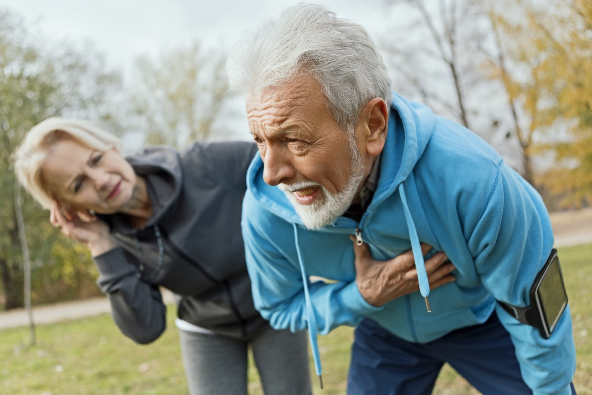 Senior man suffering heart attack while jogging with wife.