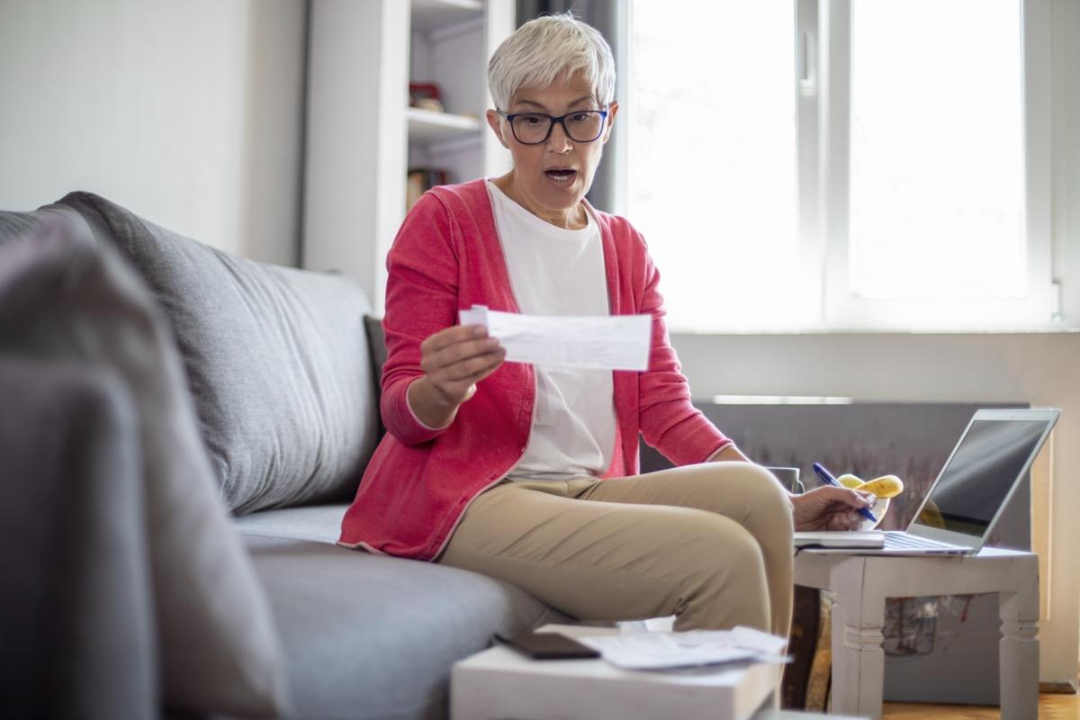 Surprised senior mature woman counting bills at home.