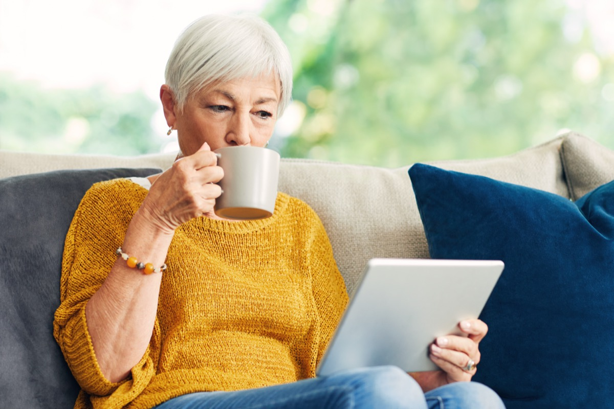 Senior woman using a digital tablet and having coffee on the sofa at home.