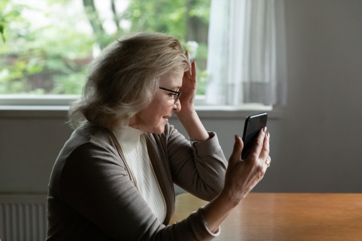 Pensioner reading message on mobile phone