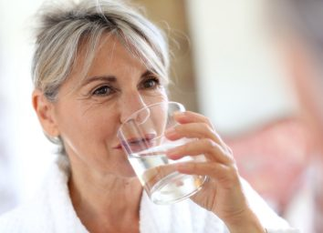 Senior woman drinking water in the morning