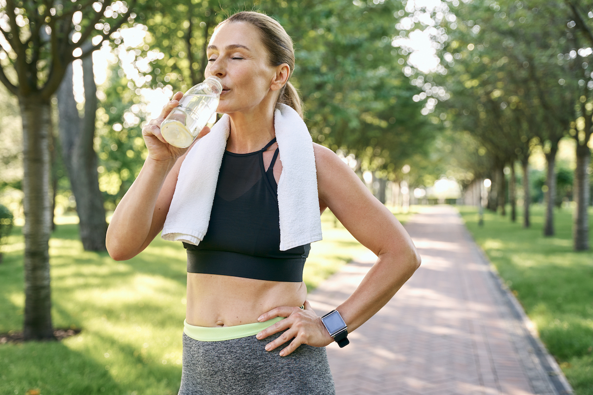 Stay hydrated.  Tired fit woman in sportswear refreshing drinking water after jogging in green park on sunny day