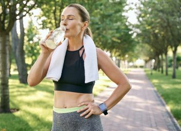 Stay hydrated. Tired fit woman in sportswear refreshing, drinking water after jogging in a green park on a sunny day