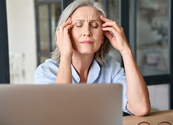Stressed middle 60s aged worker woman massaging head suffering of headache in home office.