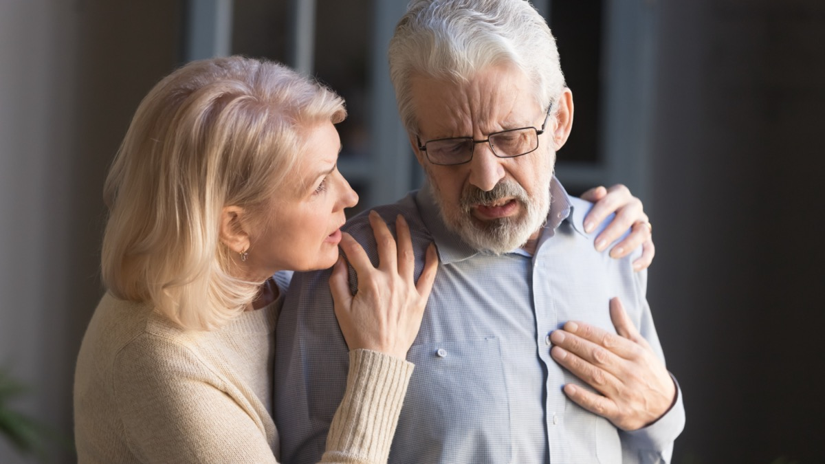 Grey haired man touching chest, feeling pain at home, mature woman supporting him.