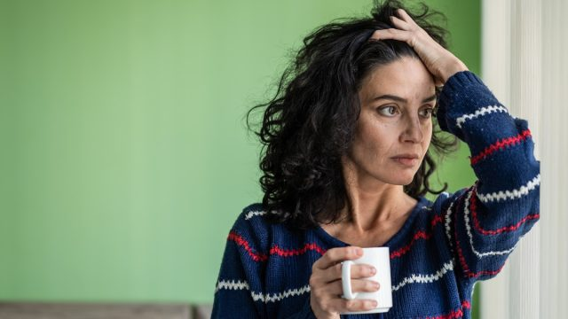 Mature woman standing home alone, worried, drinking coffee.