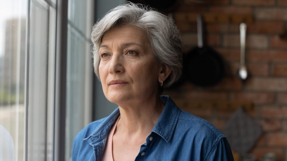 Elderly woman stands by window look away.