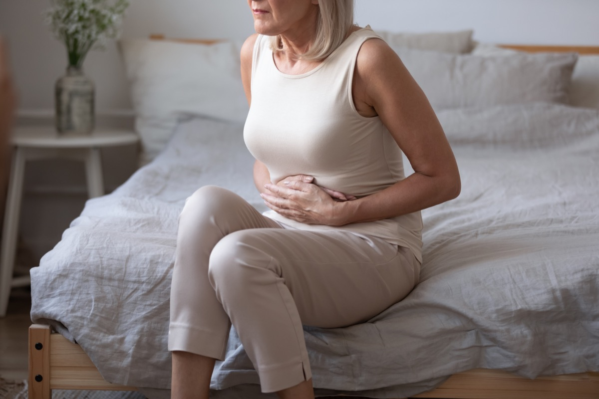 middle aged woman sitting on bed with stomach pain