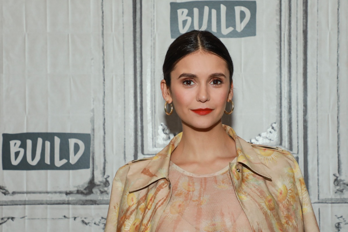 nina dobrev in tan floral outfit in front of build step-and-repeat