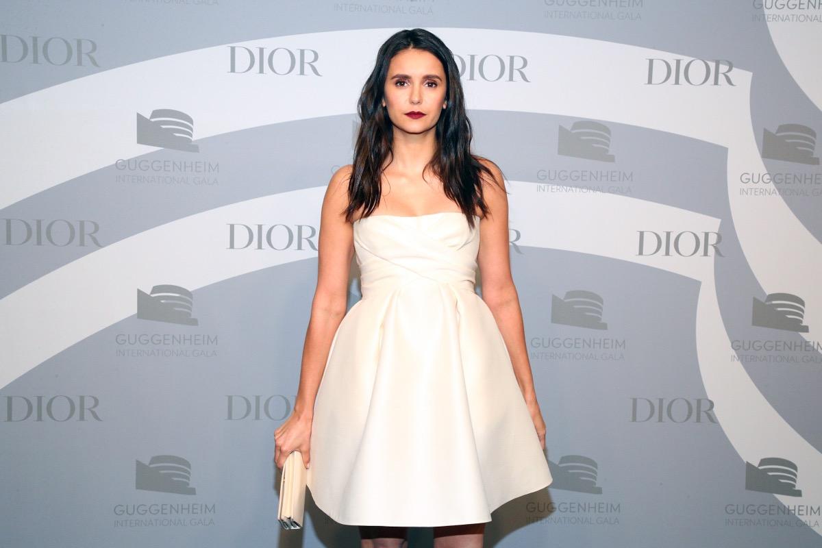 nina dobrev in white dress on red carpet