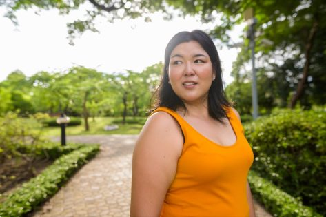 Overweight Asian woman wearing yellow orange dress relaxing in the park.