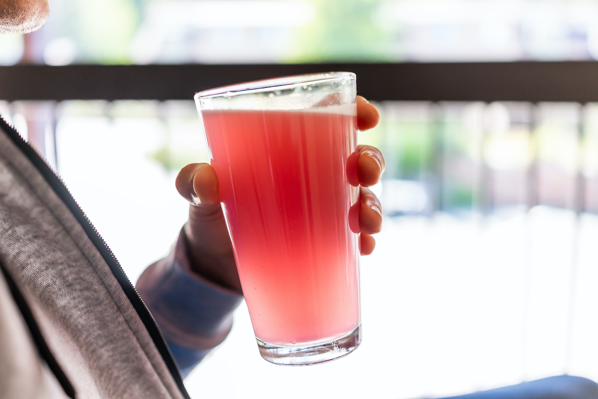 Man sitting outside holding drinking glass of red pink lemonade cocktail juice closeup of drink color