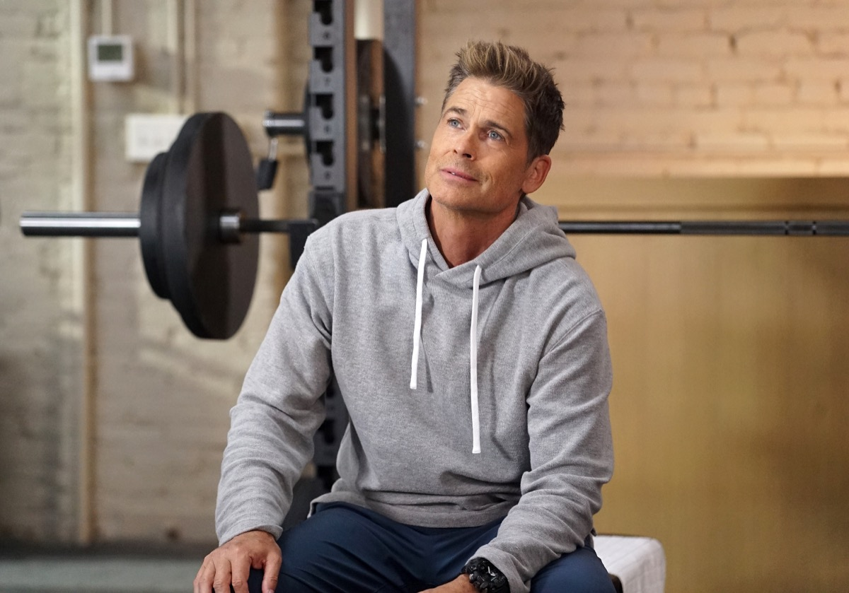 rob lowe sitting in front of weight bench