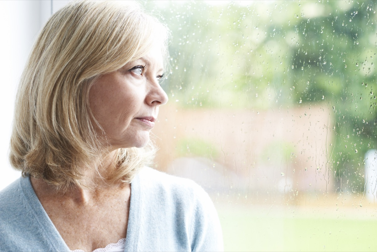 Sad mature woman looking out of window.