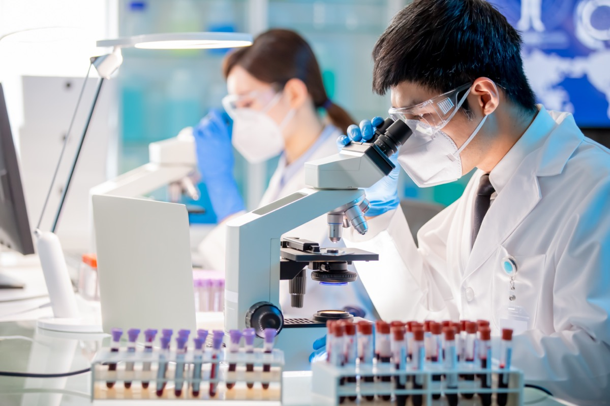 Asian microbiologist biotechnology researcher using microscope in the lab.