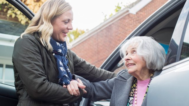 Female neighbor giving senior woman a lift In car.