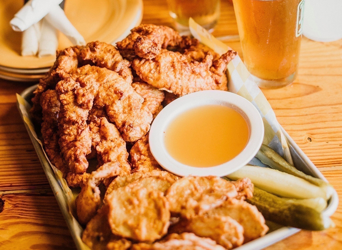 plate of chicken tenders with dip and pickles