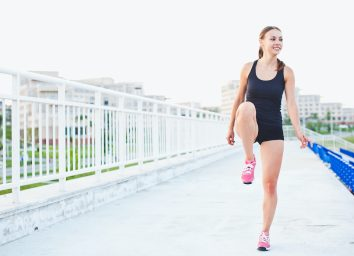 Young smiling attractive sporty girl runner in shorts and sleeveless shirt keeps her leg raised while warming up and stretching outdoors at stadium of university campus seen on background