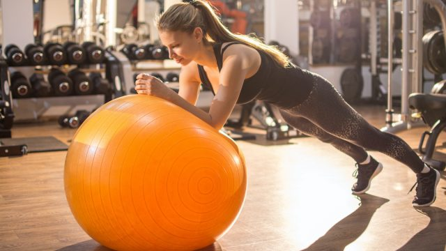 Fit girl workout with fitness ball in plank position in gym.