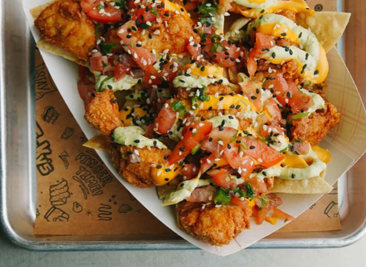stickys chicken nachos topped with tomato and sesame seeds