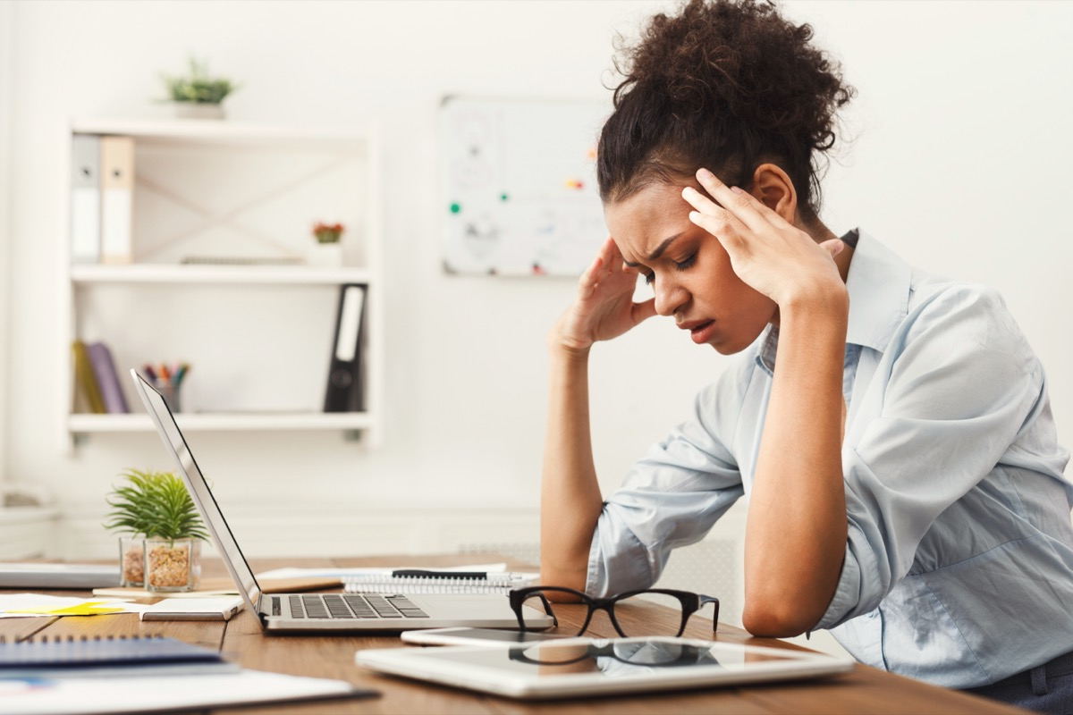 stressed out young woman sitting at desk