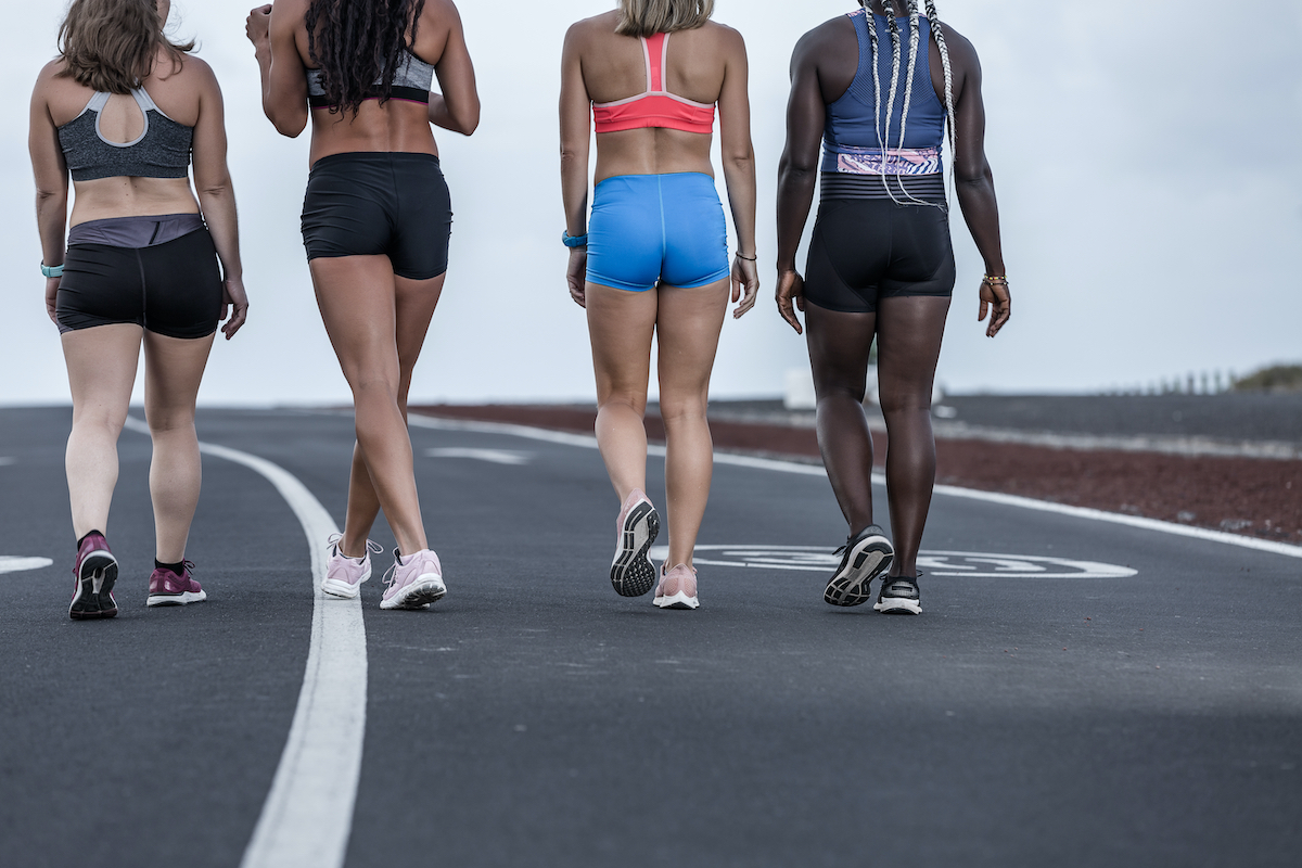 Back view of crop diverse female athletes in sportswear walking on asphalt road during outdoor workout in outskirts