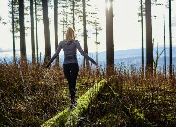 beautiful young girl walking in forest in running clothes standing on log