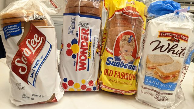 four packaged white bread loaves