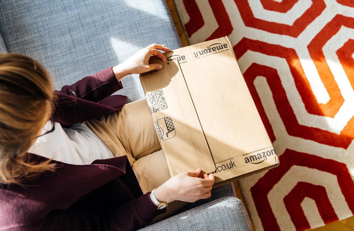 Woman unpacking unboxing Amazon cardboard box logotype printed cardboard box side.