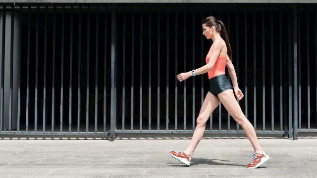 Slim sporty young girl walking on street