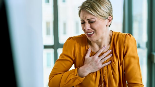 Businesswoman feeling chest pain while working in the office.