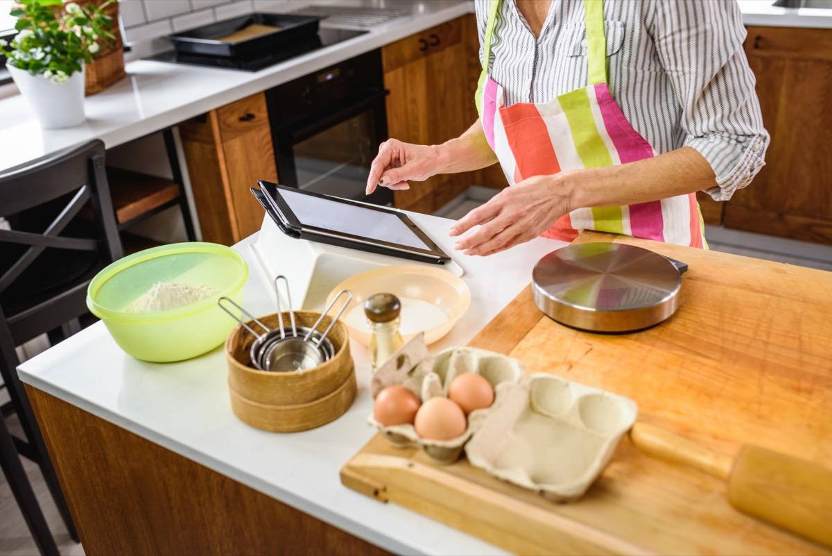 Senior aged woman baking in home kitchen.