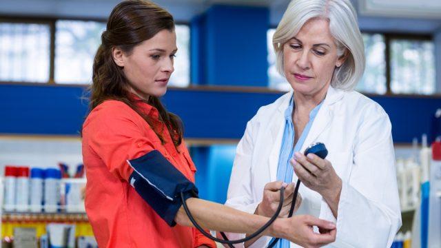 Pharmacist checking blood pressure of customer