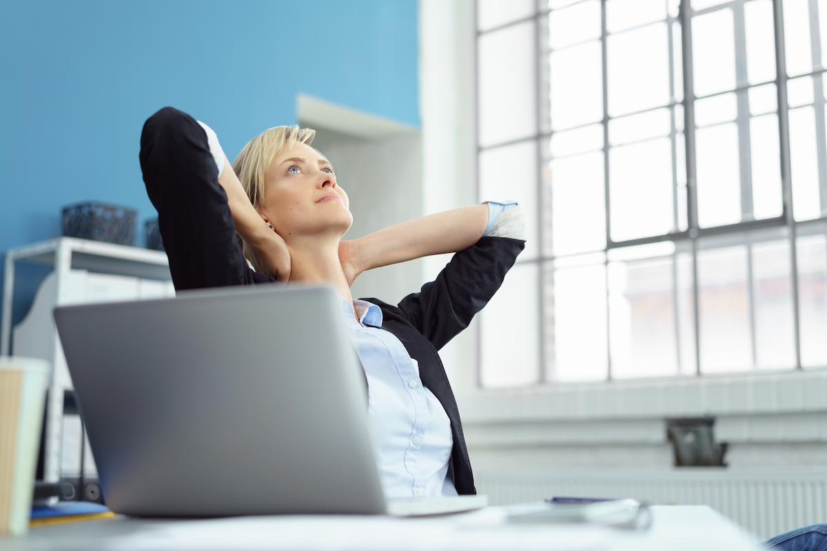 Thoughtful businesswoman taking a moment to relax leaning back in her chair staring up into the air with her hands behind her head