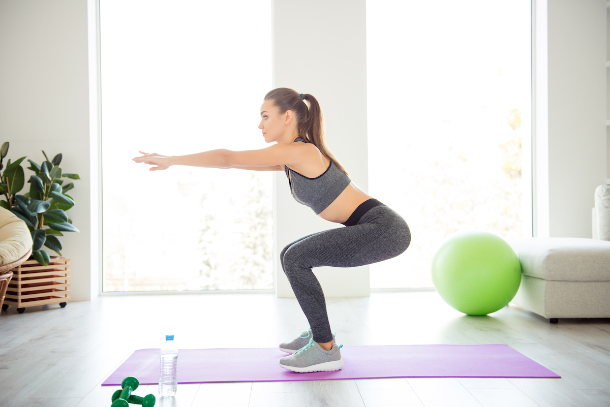 Turned half side full length size photo portrait of beautiful attractive charming confident girl doing squats in spacious large big light modern domestic gym