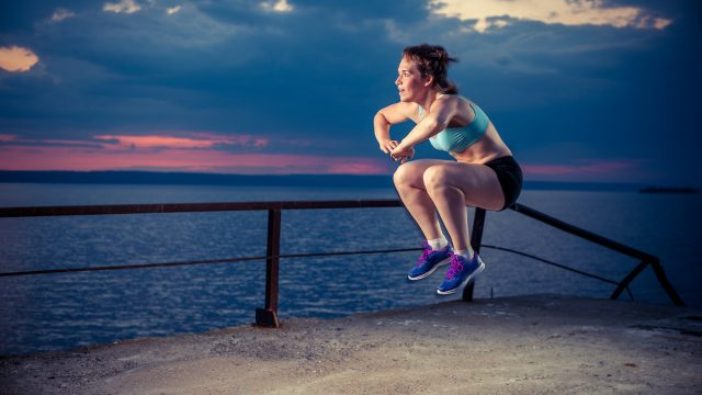 Young strong woman in sportswear doing plyometric exercises on pier. Jump squats, fitness workout outdoors.