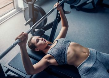 Young sports woman is working out in gym. Doing the bench press during training.