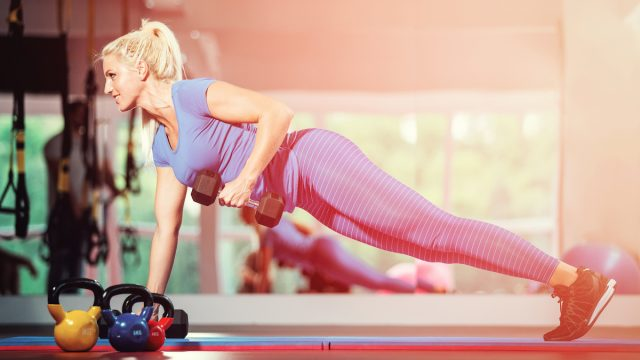 Fitness girl doing dumbbells plank row exercise lifting dumbbell weights. Woman doing floor workout renegade row or commando alternating plank row at gym.