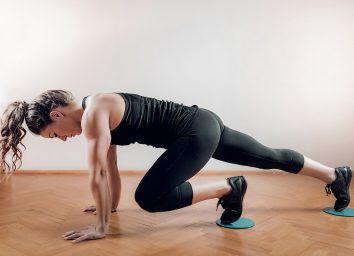 Sportswoman exercising, using Gliding Discs.