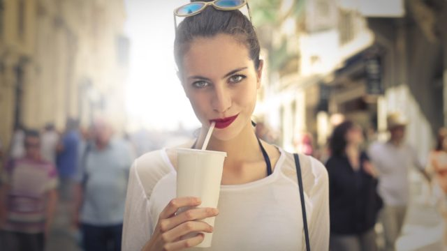 woman drinking out of white cup with straw