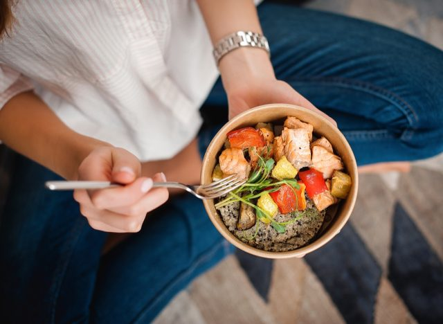 woman eating salmon and quinoa