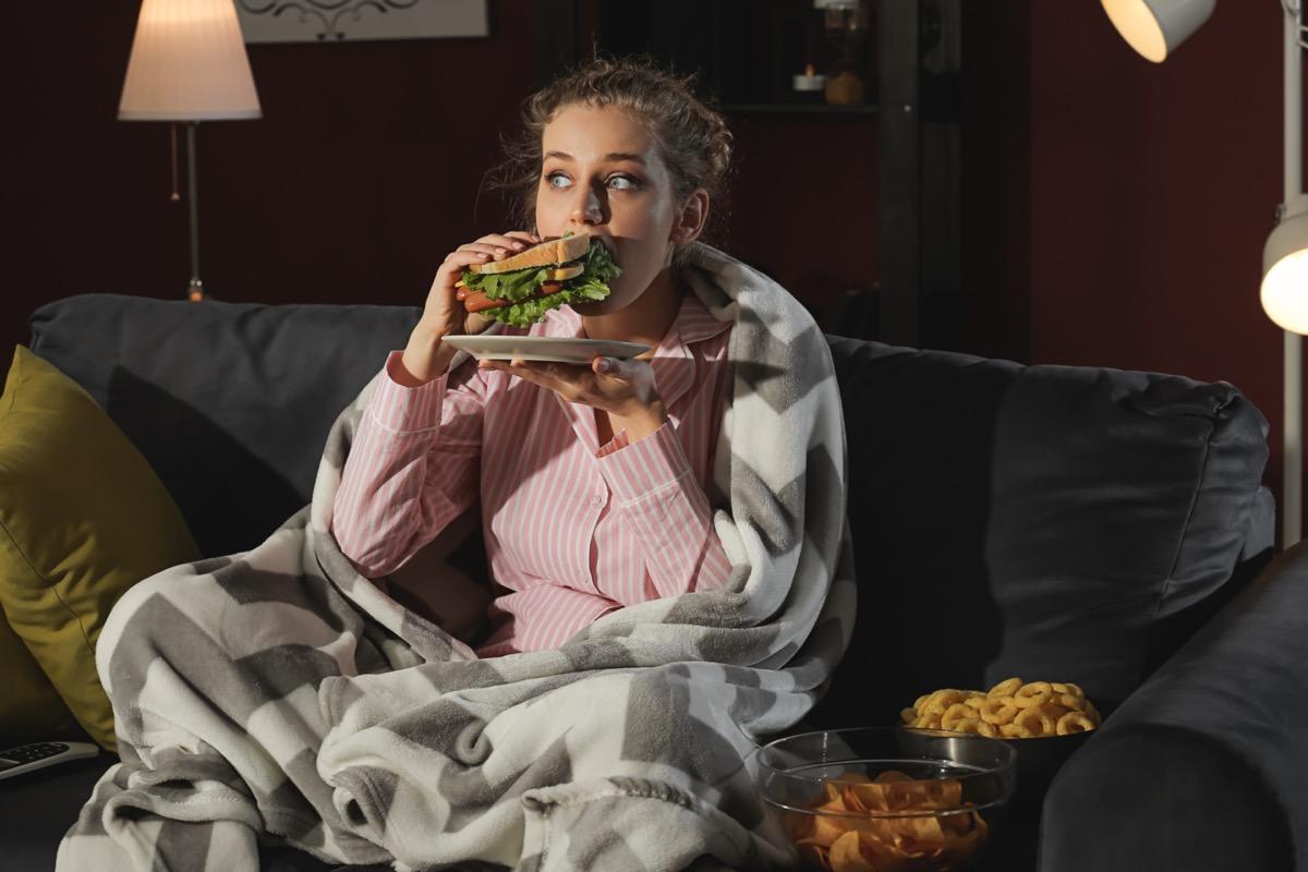 woman eating unhealthy food while watching tv at night.